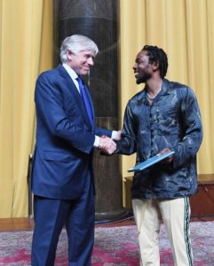 Kendrick Lamar shakes hands with Lee Bollinger