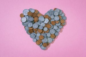 A heart made of coins on a pink background