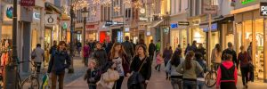 A street filled with shoppers and decorated for the holiday