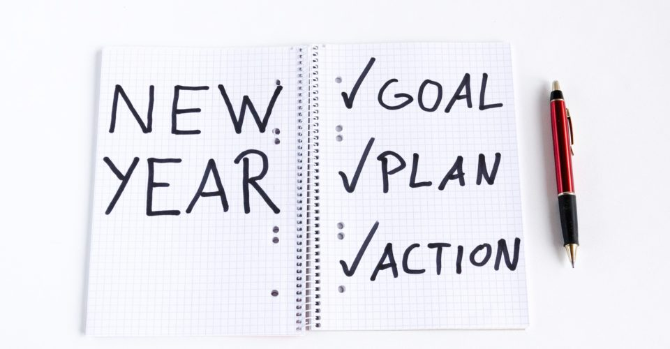 Note pad with the words New Year written on one side and the words Goal, Plan, and Action written on the other side.