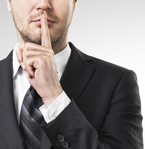 Business man with his index finger to his mouth to quiet a conversation.