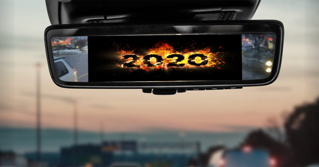 A car rearview mirror looking back at the numbers 2020 on fire.