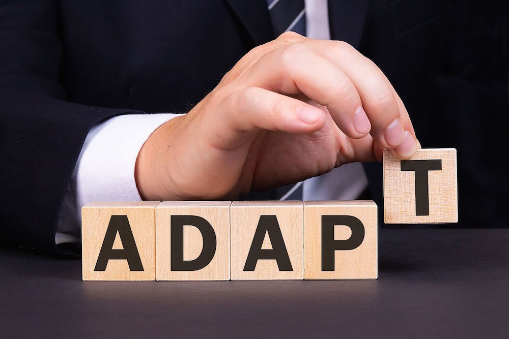 Hand placing blocks of letters together to form the word adapt.